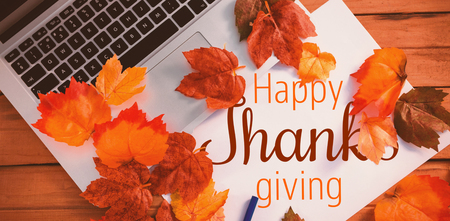 Thanksgiving greeting text against laptop coated of leaf Stock Photo