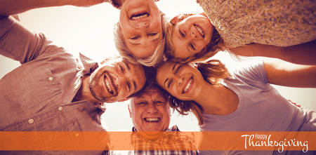 Illustration of happy thanksgiving day text greeting against happy family forming huddle against sky