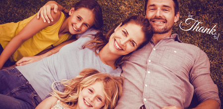 Digital image of happy thanksgiving day text greeting against portrait of happy family lying on field Stock Photo