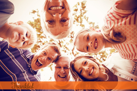 Thanksgiving greeting text against portrait of happy multi-generation family forming a huddle in park Stock Photo