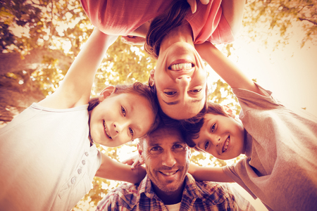 Portrait of happy family in park huddling in circle