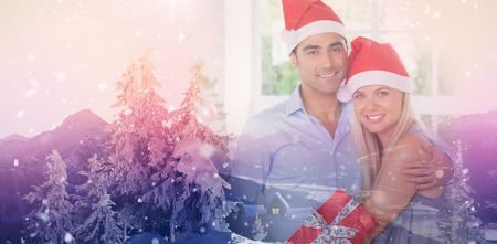 Happy couple at christmas against view of landscape during snowfall Stock Photo