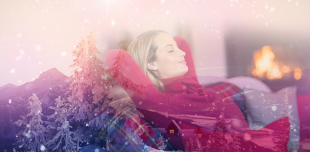View of landscape during snowfall against smiling blonde relaxing on the couch at christmas