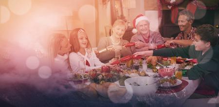 Wolken, die snowcapped Berge gegen Himmel gegen lächelnde Familie ziehen Weihnachtscracker am Abendtische bedecken