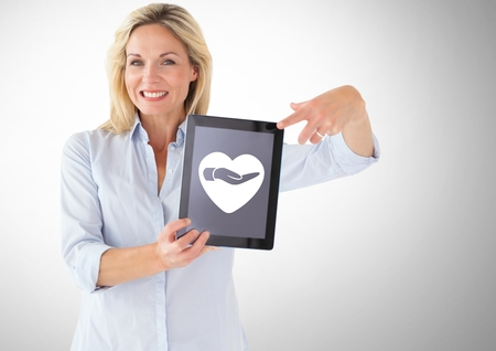 Digital composite of Woman holding tablet with heart and giving hand icon