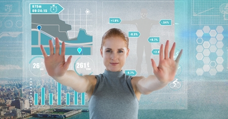 Digital composite of Data charts interface and Futuristic Businesswoman touching air in front of grey grunge city Stock Photo