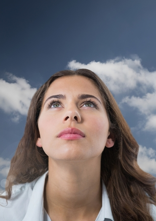 Digital composite of Woman looking up with cloudy background