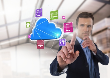 Digital composite of Cloud app interface and Businessman touching air in front of warehouse