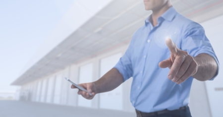 Digital composite of Businessman touching air with phone in front of warehouse