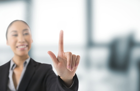 Digital composite of Businesswoman touching air in front of blurred office