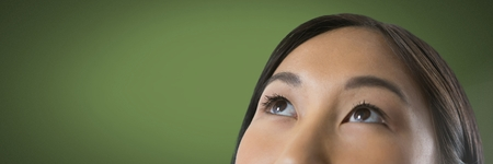 Digital composite of Woman looking up with green background Stock Photo