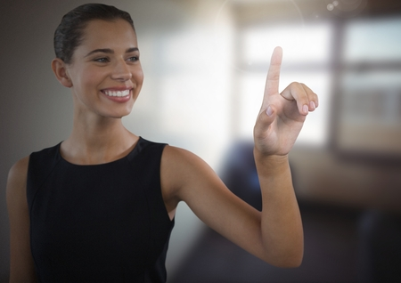 Digital composite of Businesswoman touching air in front of office Stock Photo