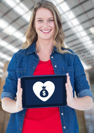 Digital composite of Woman holding tablet with money bag icon and heart icon