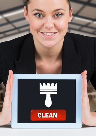 Digital composite of Woman holding tablet with clean button and brush icon
