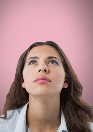 Digital composite of Woman looking up with pink background Stock Photo