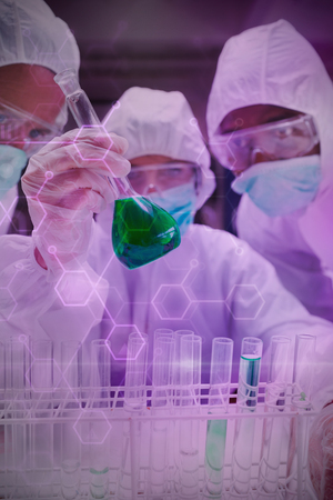 Digital data  against  chemists in protective suits looking at green liquid in beaker Chemists in protective suits looking at green liquid in beaker in the lab