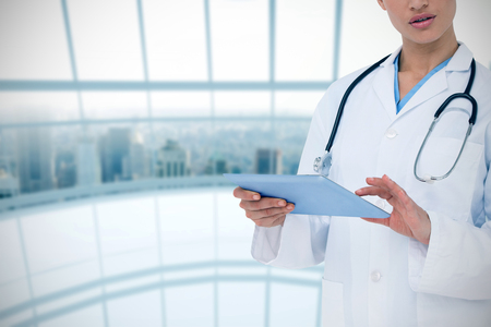 Focused doctor using her tablet pc against architectural detail of empty room Stock Photo