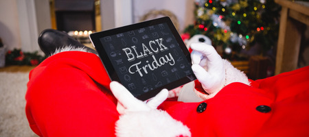 black friday against santa claus sitting and using digital tablet Stock Photo