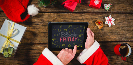 Black Friday with icons on blackboard against santa claus using digital tablet on table Stock Photo