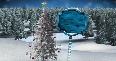 Digital composite of Wooden signpost in Christmas Winter landscape with Christmas tree Stock Photo