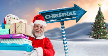 Digital composite of Christmas text and Santa holding gifts with Wooden signpost in Christmas Winter landscape with Chris Stock Photo