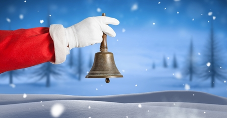 Digital composite of Santa ringing bell in Christmas Winter landscape Stock Photo