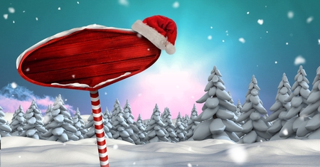 Digital composite of Wooden signpost in Christmas Winter landscape and Santa hat Stock Photo