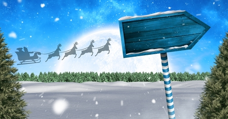 Digital composite of Wooden signpost in Christmas Winter landscape and Santas sleigh and reindeers