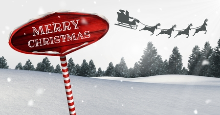 Digital composite of Merry Christmas text on Wooden signpost in Christmas Winter landscape and Santas sleigh and reindee