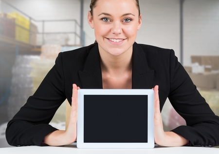 Digital composite of Woman holding tablet with stock storage room background