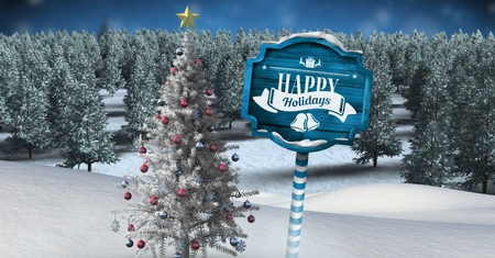 Digital composite of Happy holidays text on Wooden signpost in Christmas Winter landscape with Christmas tree