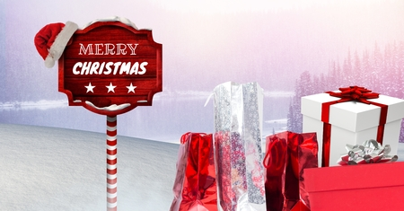 Digital composite of Merry Christmas text and gifts with Wooden signpost in Christmas Winter landscape and Santa hat