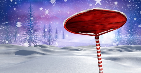 Digital composite of Wooden signpost in Christmas Winter landscape Stock Photo