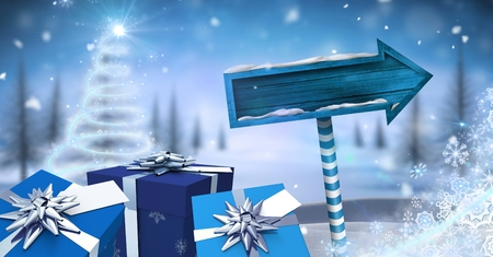 Digital composite of Gifts and Wooden signpost in Christmas Winter landscape