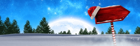 Digital composite of Wooden signpost in Christmas Winter landscape and Santa hat Imagens