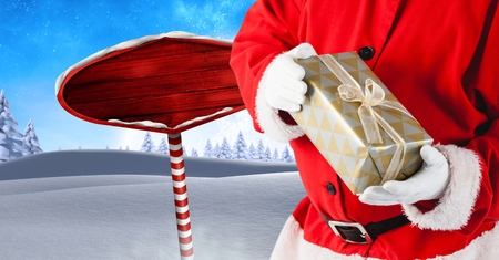 Digital composite of Santa holding gift and Wooden signpost in Christmas Winter landscape Stock Photo