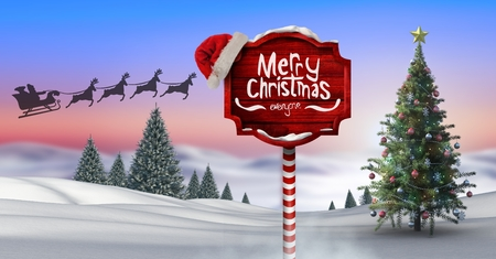 Digital composite of Merry Christmas text on Wooden signpost in Christmas Winter landscape with Christmas tree and Santa Stock Photo