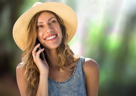 Digital composite of Woman on phone wearing hat in forest