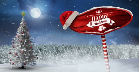 Digital composite of Happy holidays on Wooden signpost in Christmas Winter landscape and Santa hat with Christmas tree