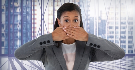 Digital composite of Businesswoman covering mouth with hand in city office Stock Photo