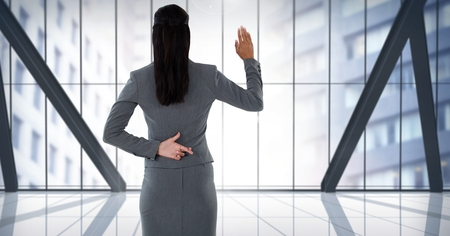 Digital composite of Businesswoman swearing honesty with hand and fingers crossed behind back in city office Фото со стока