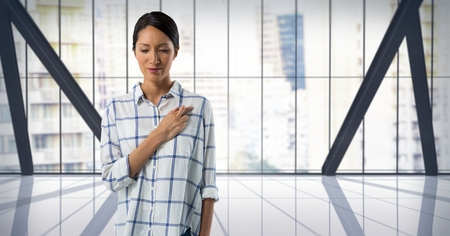Digital composite of Businesswoman swearing honesty with hand in city office