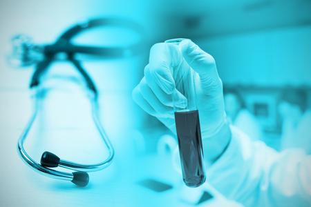 Scientist holding a test tube against stethoscope on desk