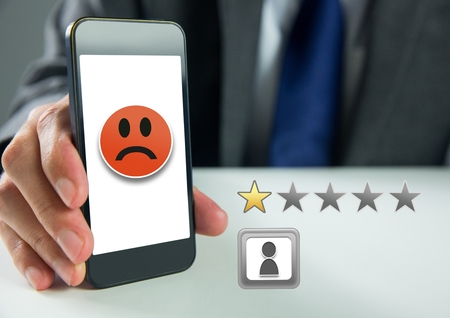 Digital composite of Hand holding phone with one star review ratings stars and sad smiley face