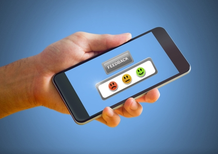 Digital composite of Hand holding phone with feedback review satisfaction smiley face icons