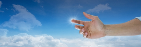 Digital composite of Hand touching sky