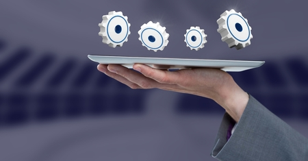 Digital composite of Hand holding tablet with 3D cog icons Stock Photo