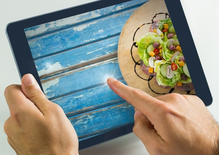 Digital composite of Hand touching tablet with food