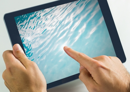 Digital composite of Hand touching tablet with water in swimming pool