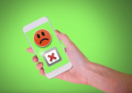 Digital composite of Hand holding phone with sad smiley face and X negative wrong button
